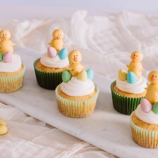 A cupcake with an easter chick made of fondant and candy eggs for the cutest Easter dessert.